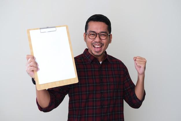 Homem asiático adulto segurando um papel branco em branco e mostrando uma expressão facial feliz