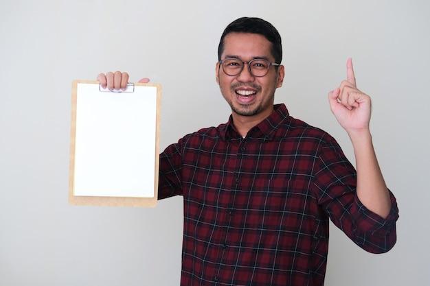Homem asiático adulto segurando um papel branco vazio em um bloco de notas com uma expressão de rosto sorridente