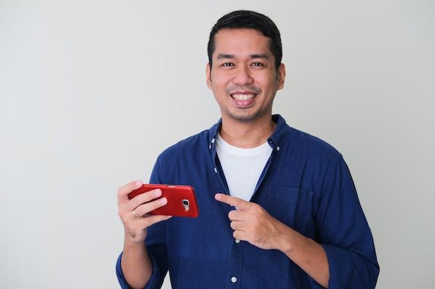 Homem asiático adulto sorrindo enquanto aponta o dedo para seu telefone celular