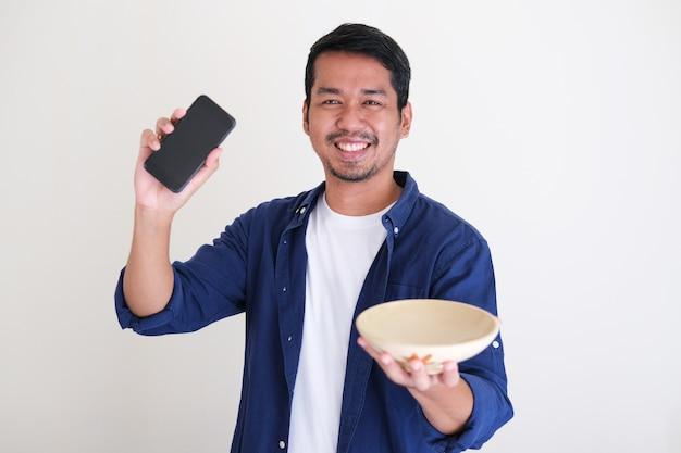 Homem asiático adulto sorrindo, segurando uma tigela de comida vazia e um telefone celular