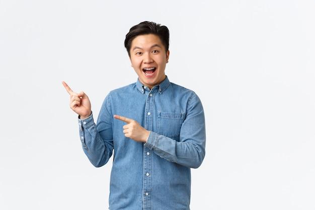 Homem asiático alegre animado de camisa azul reage a notícias fantásticas, apontando o dedo no canto superior esquerdo