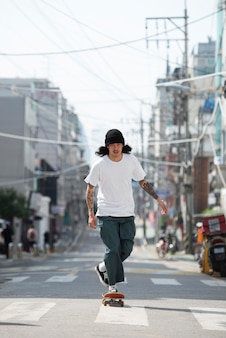 Homem asiático andando de skate ao ar livre