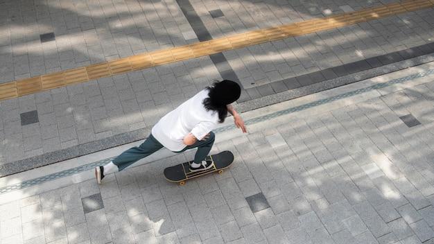 Homem asiático andando de skate na cidade