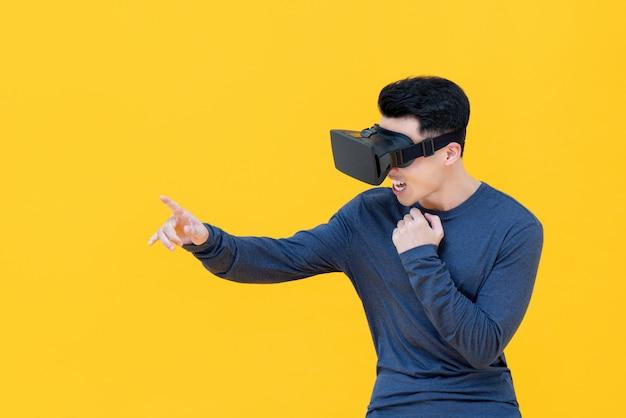 Homem asiático animado, estendendo a mão tocando algo enquanto assistia vídeo de simulação em 3d de realidade virtual ou óculos de vr na parede amarela