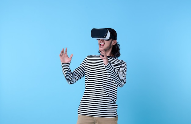 Homem asiático animado usando óculos de realidade virtual, assistindo a filmes em azul.