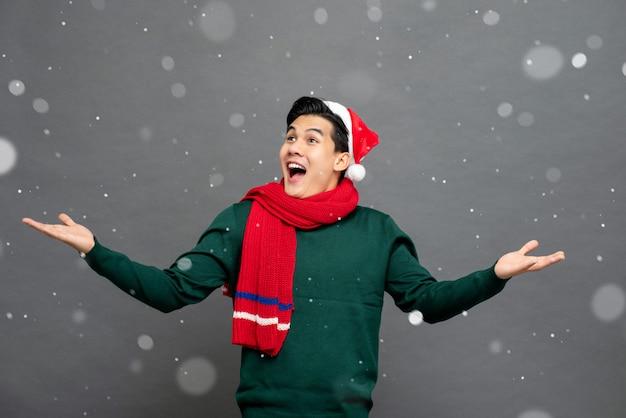 Homem asiático animado usando roupas de tema de natal com as palmas das mãos abertas gesto