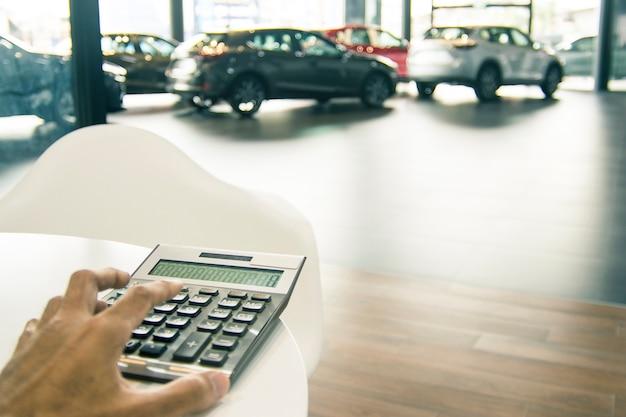 Homem asiático, apertando, calculadora, para, finanças empresariais, carro, showroom, fundo obscuro