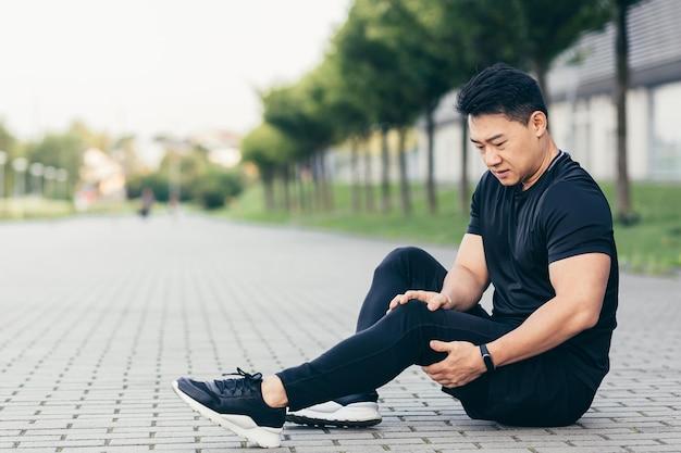 Homem asiático, após exercícios físicos e corrida, senta-se no chão e sente dores nas pernas, massageia os músculos das pernas