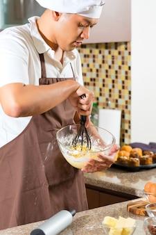 Homem asiático assando bolo na cozinha de casa