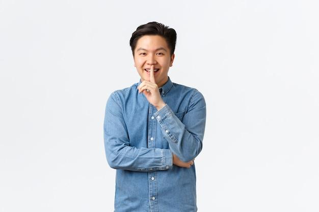 Homem asiático astuto sorridente preparando surpresa, pedindo para ficar quieto, calar ou calar a pessoa, pressionar o dedo indicador nos lábios, prometer não contar, fofocar sobre fundo branco, sussurrar.