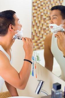 Homem asiático barbear na frente do espelho
