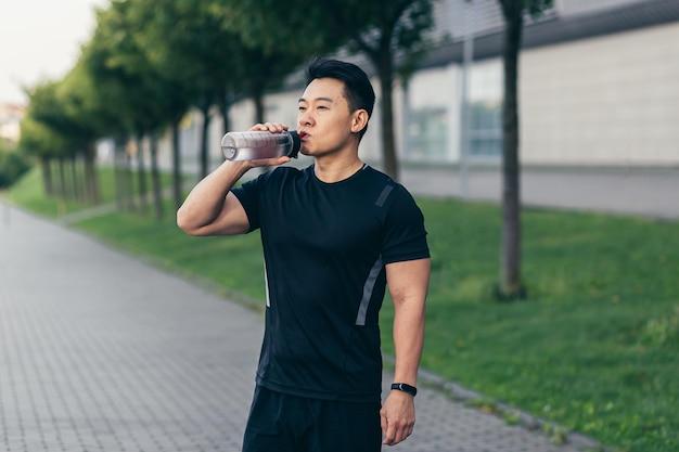 Homem asiático bebe água após exercício físico e corrida cansada