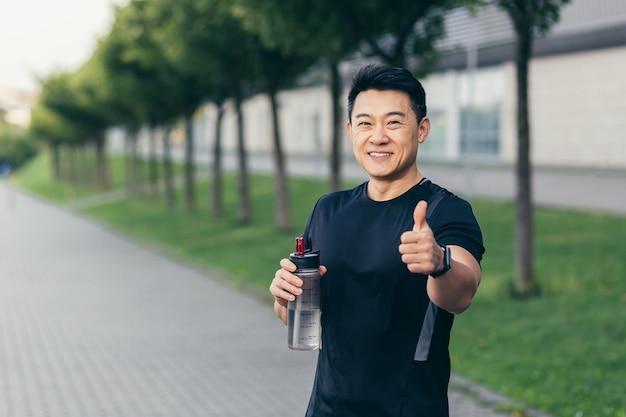 Homem asiático bebe água após treino de fitness e corrida. homem feliz sorri mostra o polegar e olha para a câmera