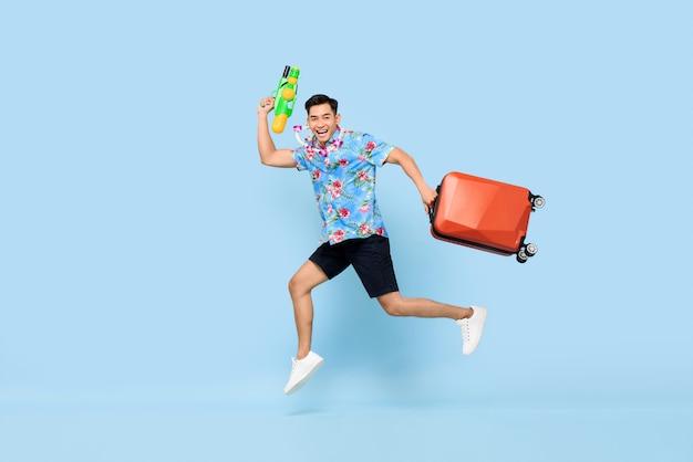 Homem asiático bonito de salto viajando com pistola de água e bagagem durante o festival songkran