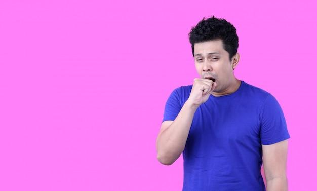 Homem asiático bonito entediado bocejando cansado cobrindo a boca com a mão. inquieto e sonolência. no fundo rosa em estúdio com espaço de cópia.