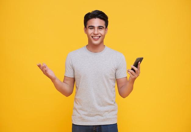 Homem asiático bonito feliz comemorando com telefone celular isolado sobre fundo amarelo.