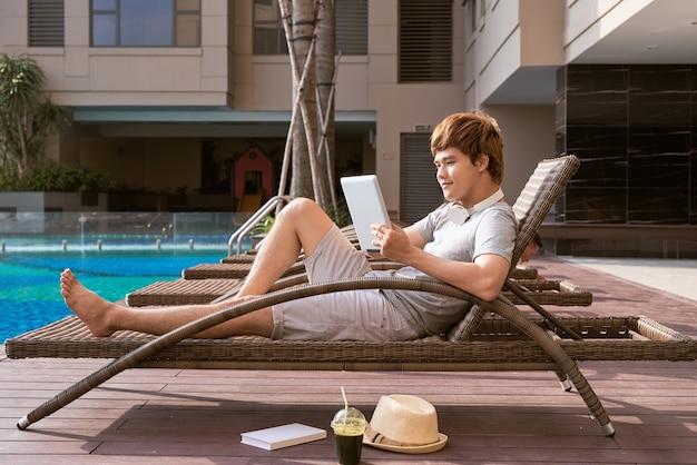 Homem asiático bonito relaxando na piscina e lendo e-book
