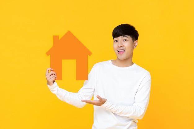 Homem asiático bonito sorridente segurando placa de casa