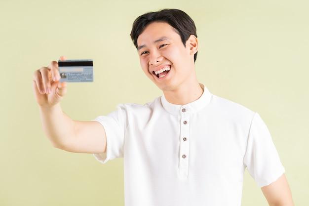 Homem asiático bonito sorrindo e olhando para o cartão de crédito na mão