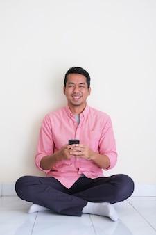 Homem asiático bonito sorrindo e sentado no chão enquanto usa seu telefone celular
