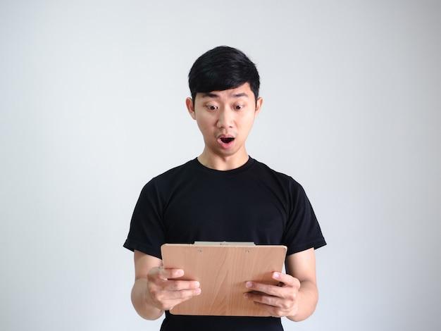 Homem asiático camisa preta com rosto chocado e olhando para a prancheta de madeira na mão no fundo branco