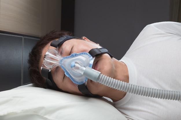 Homem asiático com apnéia do sono usando máquina de cpap