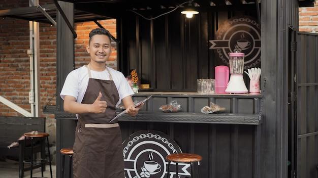 Homem asiático com avental de bar carregando um sinal de lista de menu ok em um recipiente tema angkringan