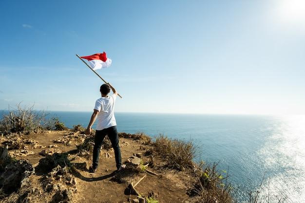 Homem asiático com bandeira da indonésia no topo da montanha