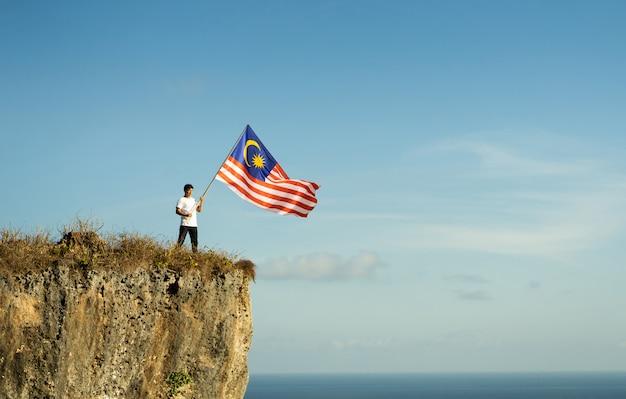 Homem asiático com bandeira da malásia comemorando o dia da independência