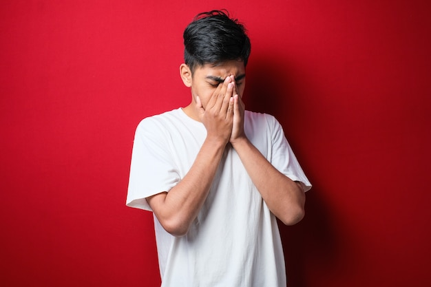 Homem asiático com bigode, vestindo camiseta branca com expressão triste, cobrindo o rosto com as mãos enquanto chora. conceito de depressão sobre fundo vermelho
