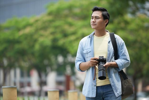 Homem asiático com câmera profissional andando pelo parque e olhando ao redor