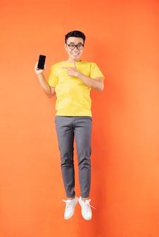 Homem asiático com camiseta amarela pulando na parede laranja