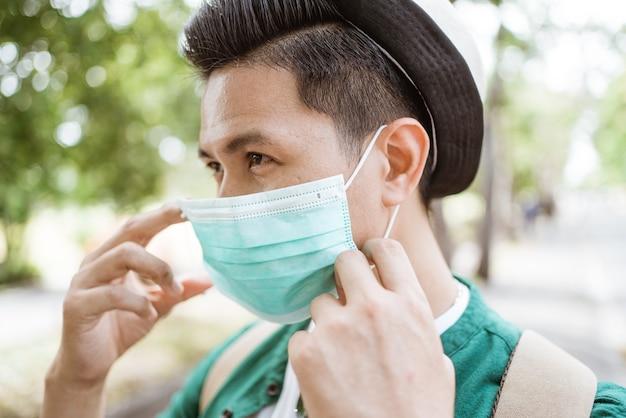 Homem asiático com coronavírus colocando uma máscara médica descartável para evitar vírus