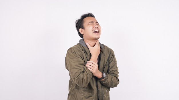 Homem asiático com dor de garganta e toca o pescoço em um espaço em branco