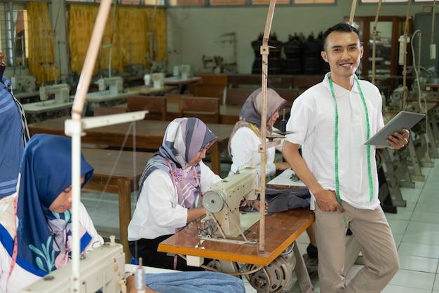 Homem asiático com fita métrica em volta do pescoço segurando um tablet pc de pé