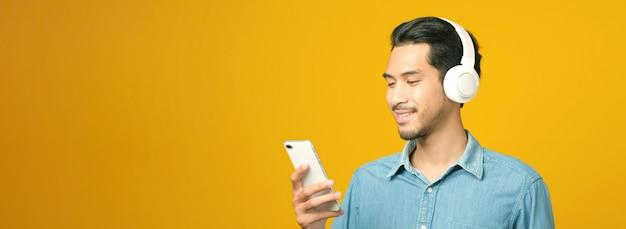 Homem asiático com fones de ouvido, segurando um telefone celular, sorrindo enquanto ouve música isolada em um fundo amarelo com espaço de cópia