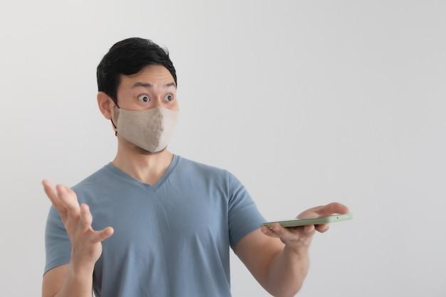 Homem asiático com máscara está feliz com a expressão de surpresa olhando para o smartphone.