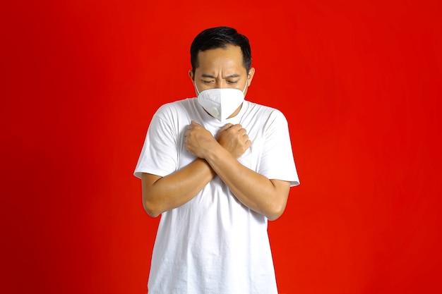 Homem asiático com máscara médica, abaixando a cabeça com as mãos cruzadas e cerradas em punho