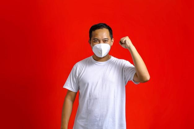 Homem asiático com máscara médica se animando com um punho cerrado sobre um fundo vermelho