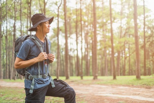 Homem asiático com mochila caminhadas na floresta