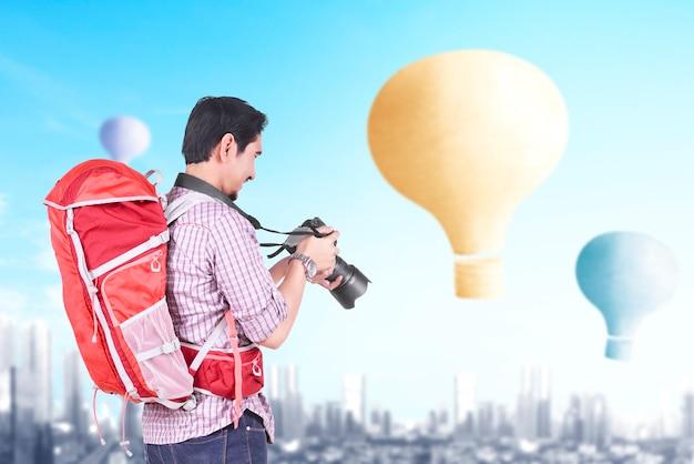 Homem asiático com mochila e câmera olhando para um balão de ar colorido voando com o fundo da cidade