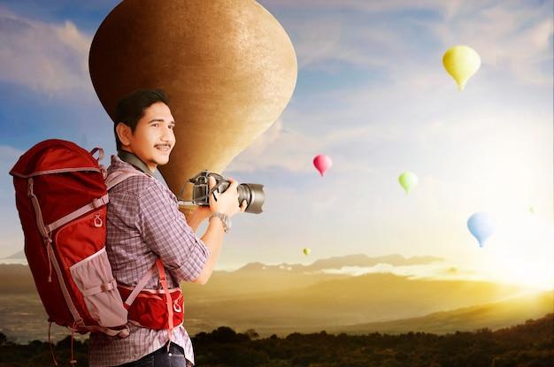 Homem asiático com mochila e câmera olhando para um balão de ar colorido voando com o fundo do céu ao pôr do sol