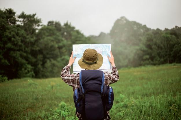 Homem asiático com mochila e chapéu na montanha