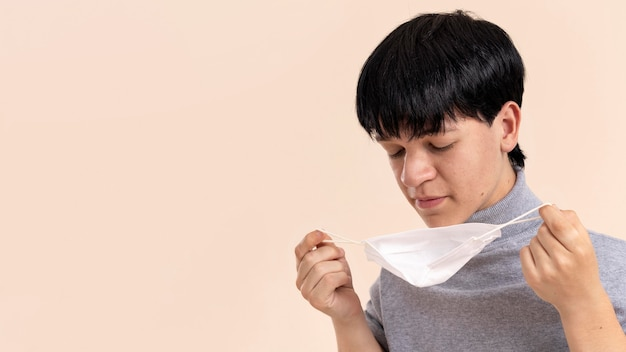 Homem asiático com nanismo segurando uma máscara médica