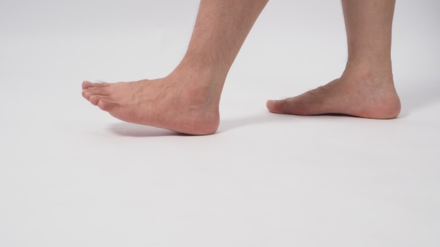 Homem asiático com os pés descalços é isolado no fundo branco.
