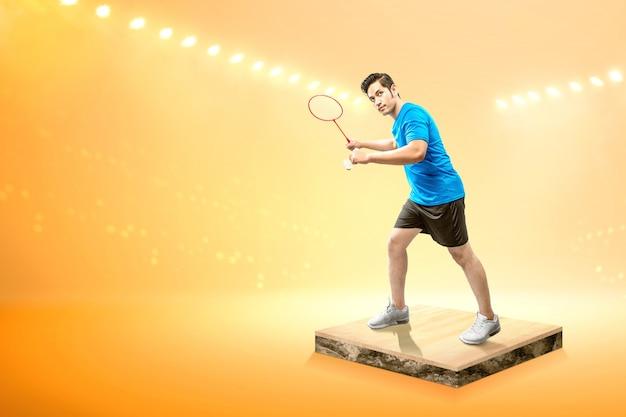 Homem asiático com raquete de badminton segurando a peteca e pronto na posição de servir