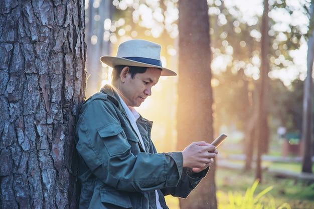 Homem asiático com telefone móvel na natureza da árvore de floresta - pessoas na natureza da mola e no conceito da tecnologia