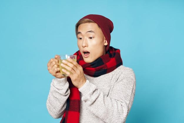Homem asiático com um cachecol e chá