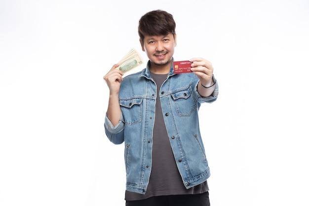 Homem asiático com um sorriso no rosto segurando um cartão de crédito e dólares no banco