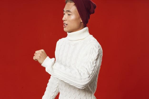 Homem asiático com um suéter branco sobre um fundo vermelho e um chapéu na cabeça copie o espaço
